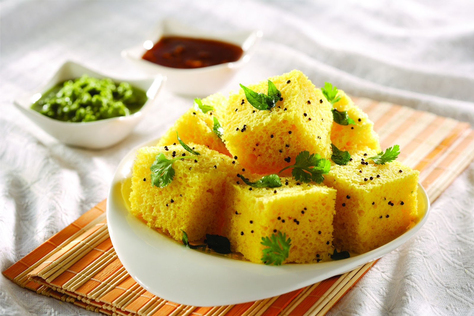 Dhokla is a vegetarian made from a fermented batter of rice and split chickpeas. It is served as a snack with tangy chutneys.