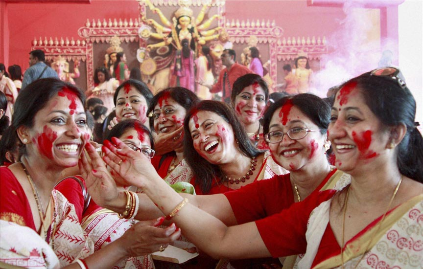 Gurgaon: Women participate in Sindur Khela (playing with vermilion powder) at a community puja pandal on the last day of Durga puja celebrations in Gurgaon on Saturday. PTI Photo(PTI10_4_2014_000046B)